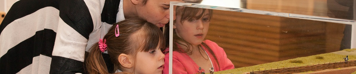 A woman and two young girls look in wonder at an exhibit