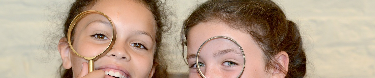 Two young girls smile as they spy with magnifying glasses they've made at a craft activity